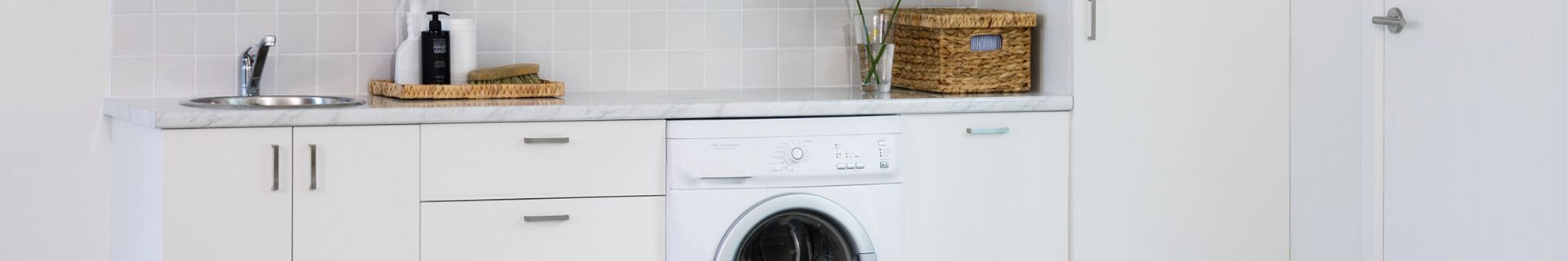 Laundry with washing machine and cupboards.
