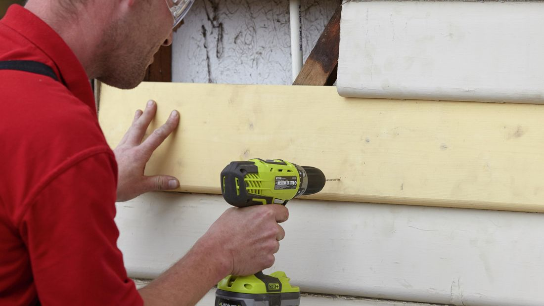 A replacement weatherboard being drilled into with a power tool