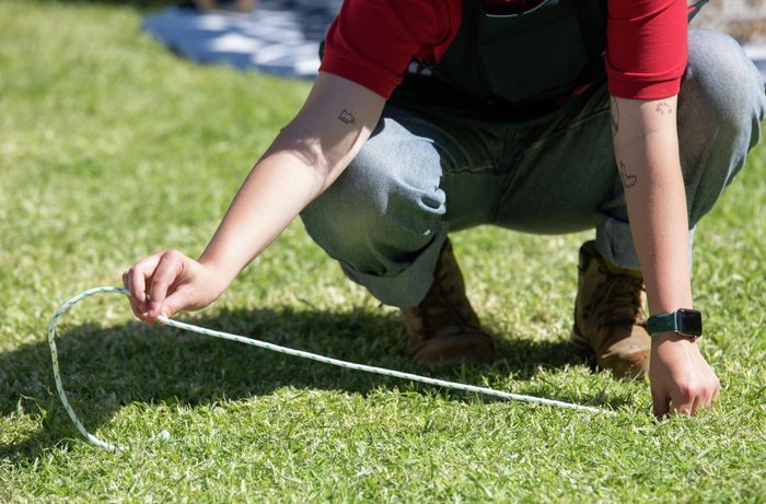 Person lining up string on the grass.