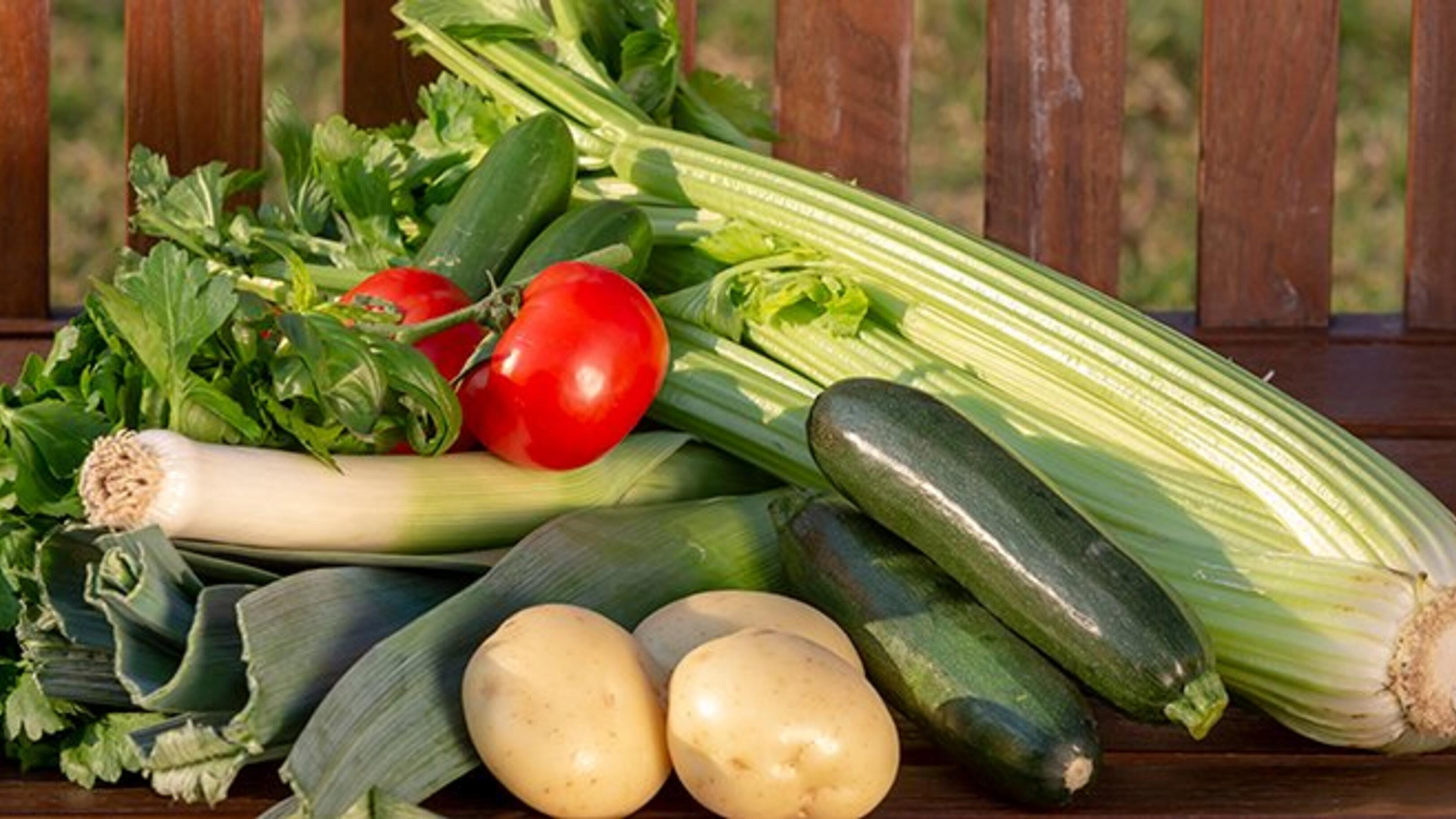 Harvested vegetables including celery, courgettes, potatoes, leeks and tomatoes.