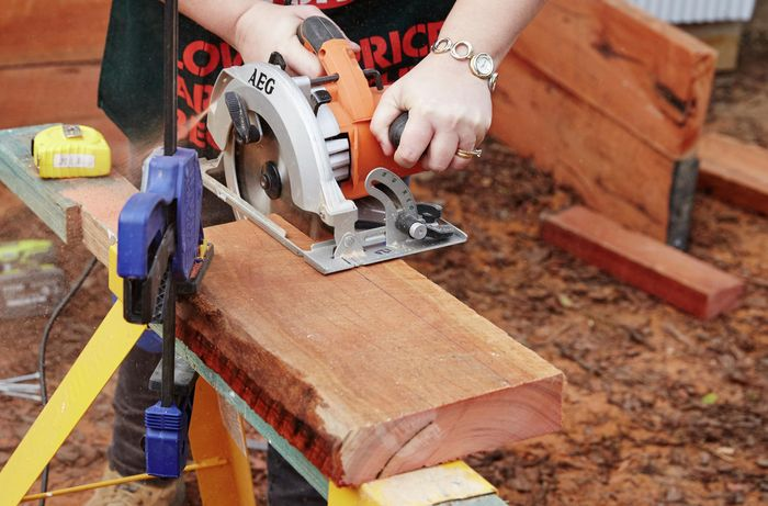 Pieces of timber to be used as gates for a sleeper compost bin being cut with a circular saw while held down with a clamp