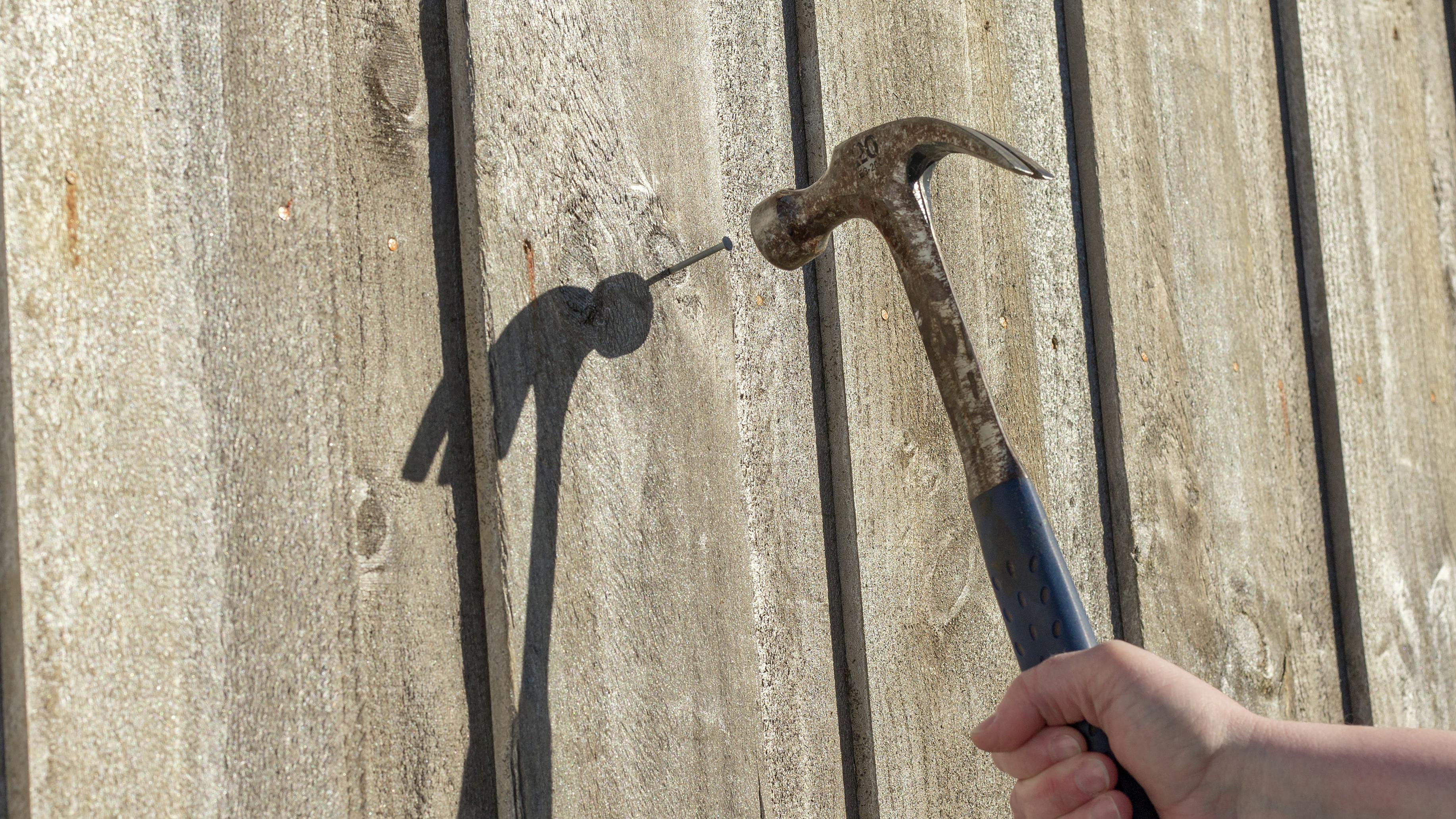 Person hammering a nail into a wooden fence.