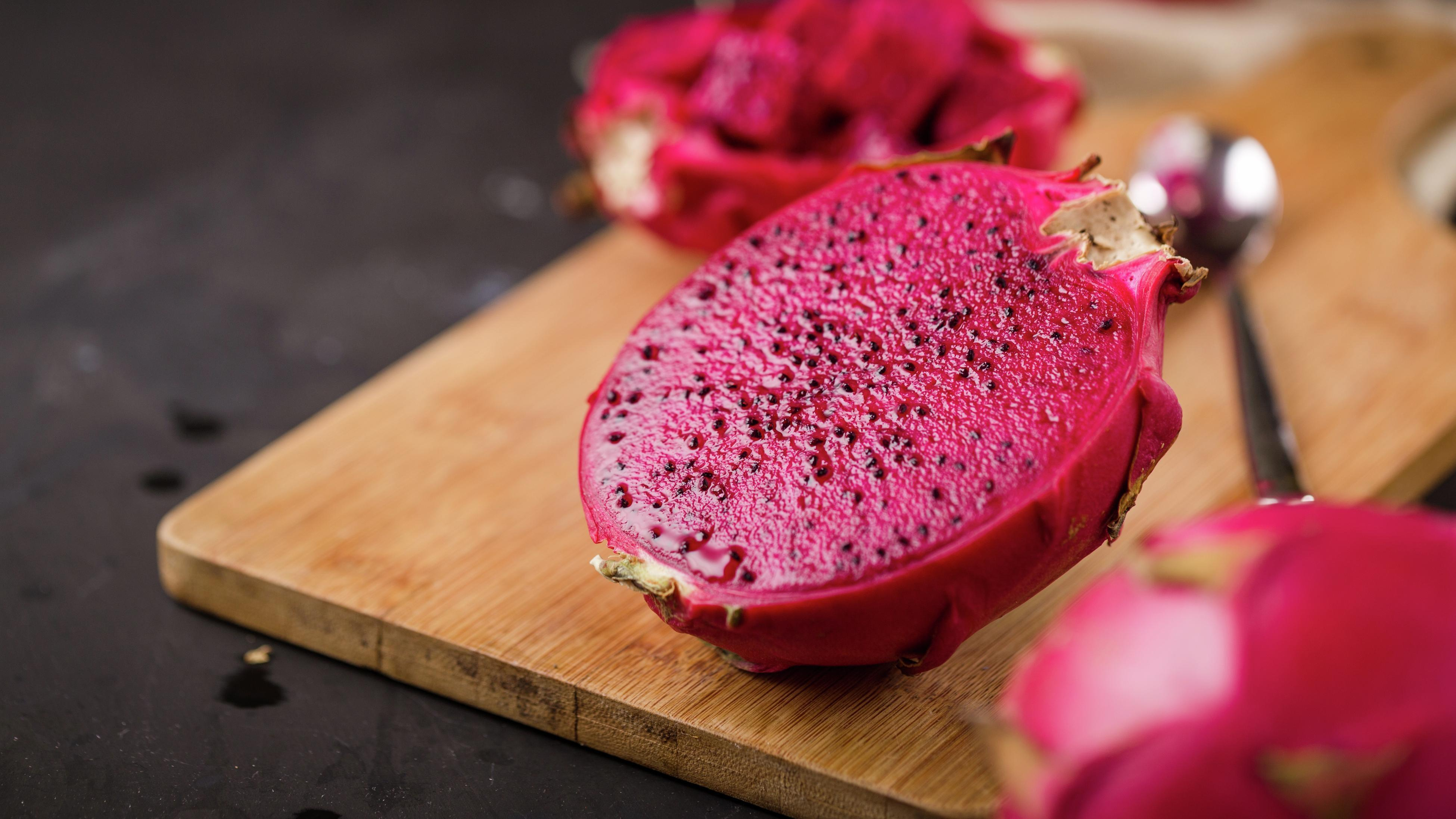 close up of a dragon fruit sliced in half on a wooden board