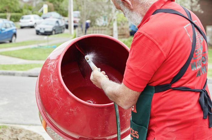 A person spraying water into a concrete mixer