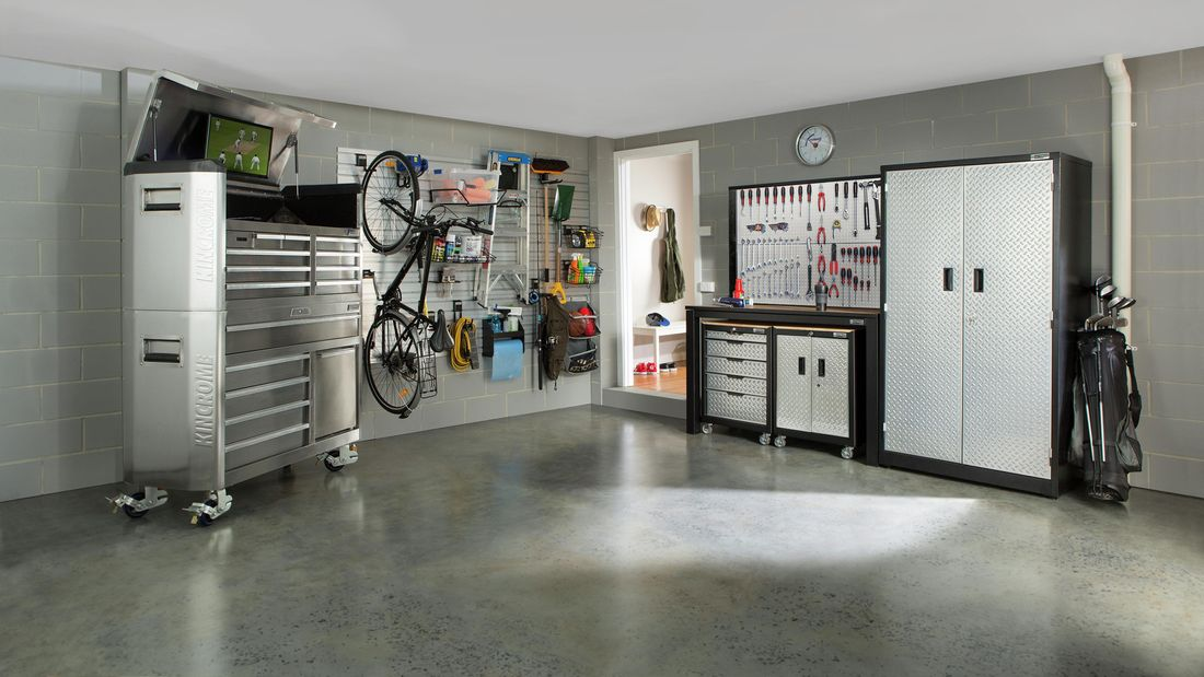 A grey themed garage with a toolchest with television, workbench, tool pegboard, storage rack, wheeled cabinet and golf club bag