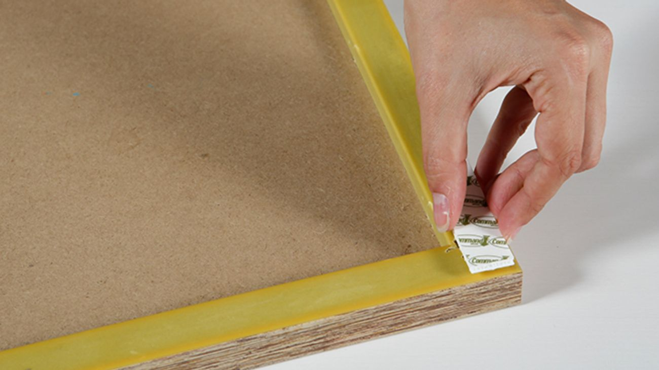 Sticking on a removable picture hanging strip to the back of a photo frame.