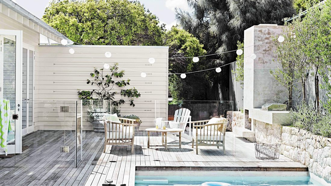 Outdoor entertaining area with deck, pool and hanging festoon lights.