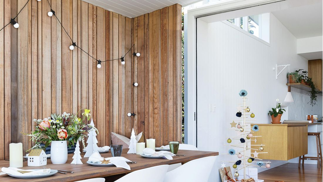 Outdoor entertaining area with table set up with dining utensils and Christmas decorations.