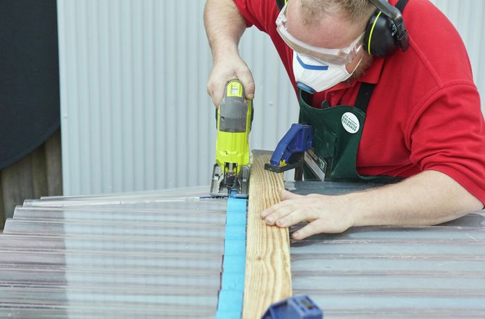 Person sawing through polycarbonate material.