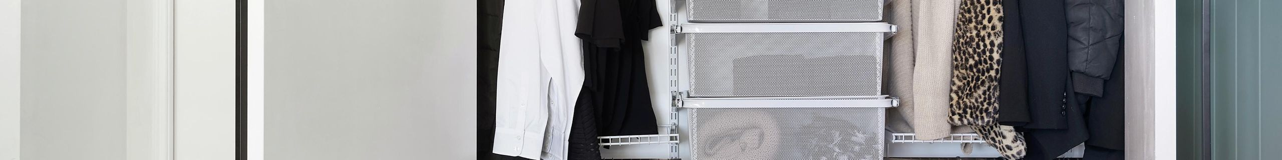 A neatly organised wardrobe with hanging rails, shelves, baskets and a pegboard