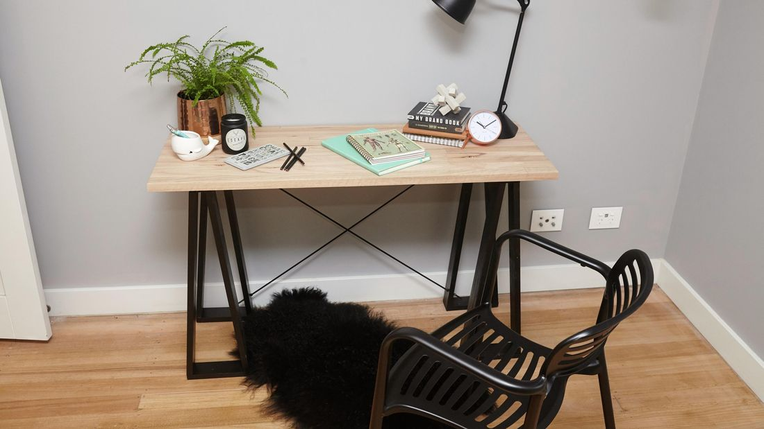 A timber trestle table on black A-frame legs