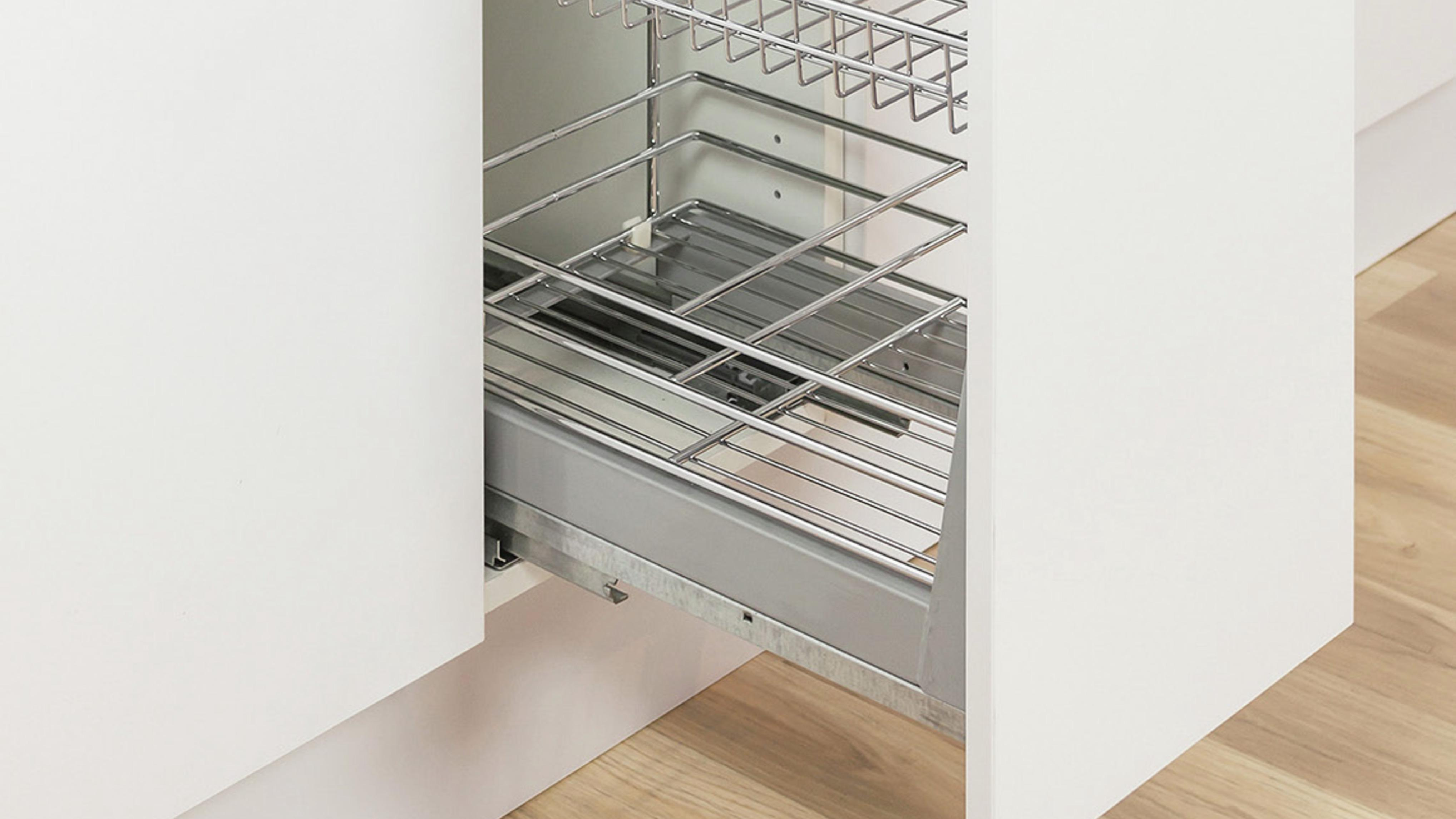 Kitchen cabinet drawer half pulled out, showing the slide out baskets inside.
