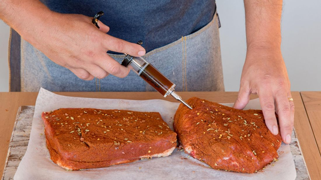 Person injecting meat with a marinade injector