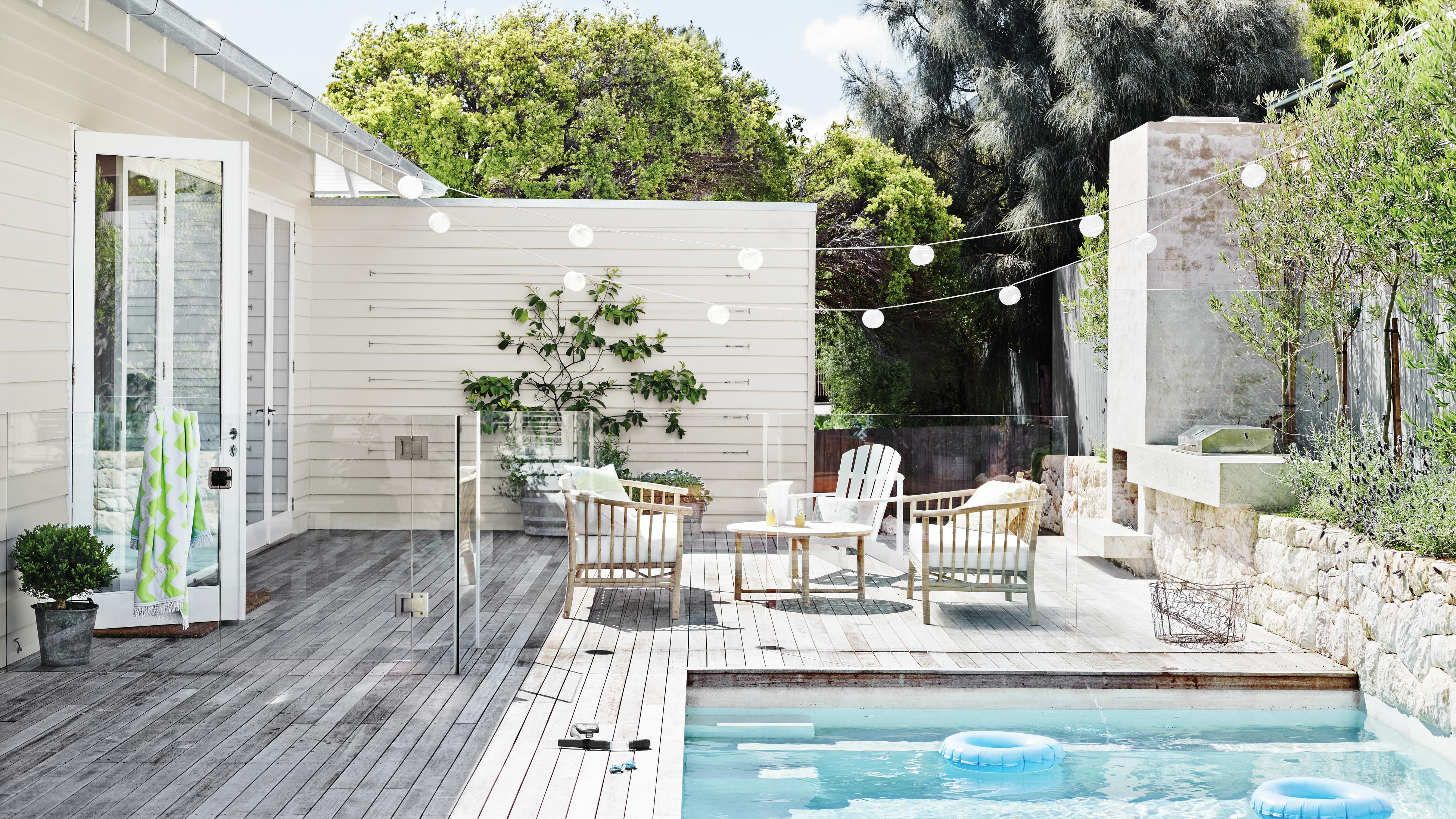 Outdoor pool area with decking, furniture, plants.