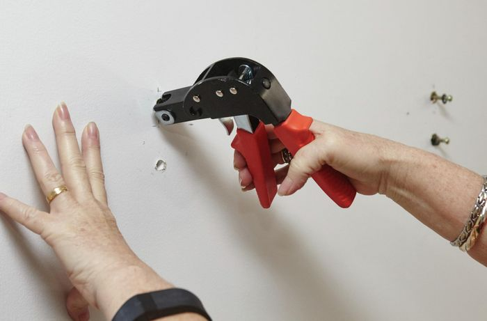 A person inserting wall anchors using a wall anchor setting tool