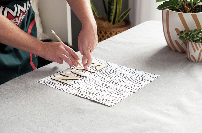 Person tracing the word FUN onto spotted paper.