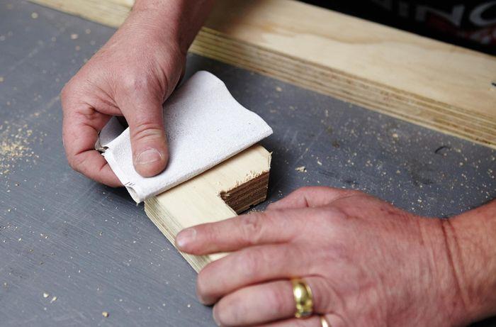 Person sanding timber bracket.