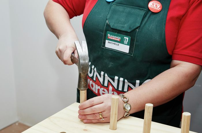 A person using a hammer to insert dowel into holes in a plywood sheet