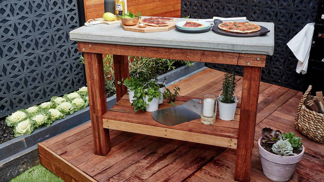 Outdoor table with food on tabletop and herbs on shelf beneath.