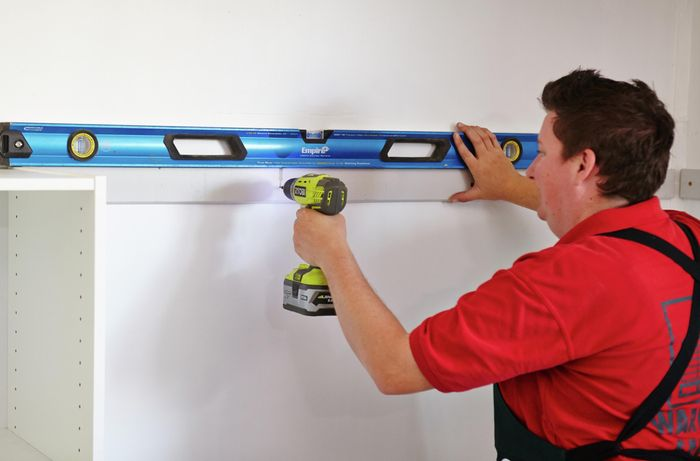 Person using spirit level to ensure cleat is drilled into wall straight.