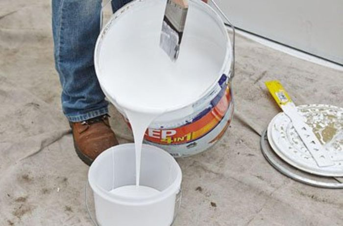 Person pouring paint into a smaller bucket.