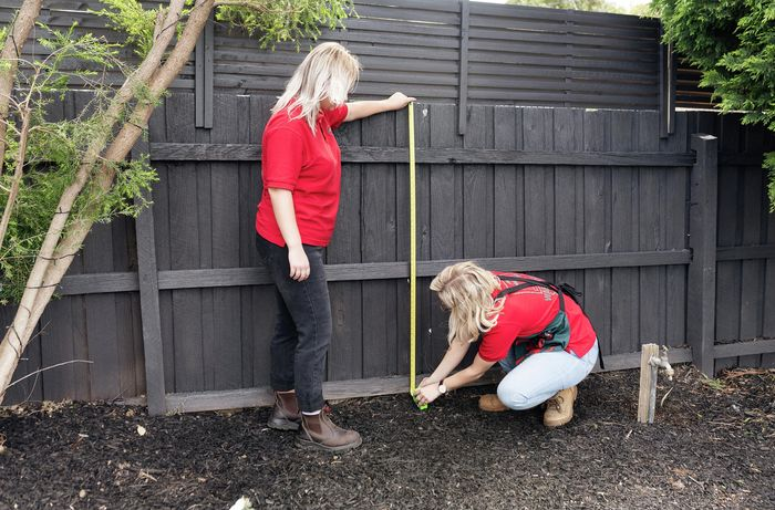 Person measuring fence.