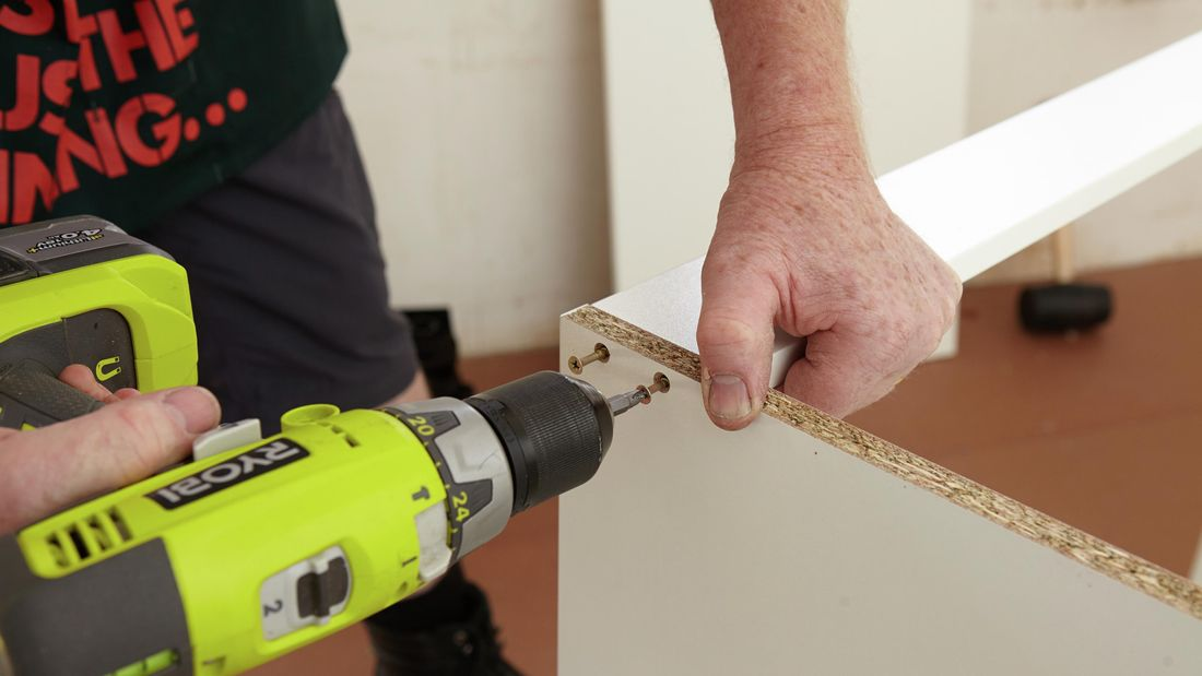 Person using a cordless driver to attach two cabinet panels
