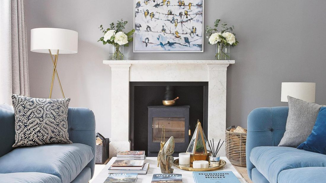 Lounge interior with plush pastel blue couches, cushions, coffee table and fireplace.