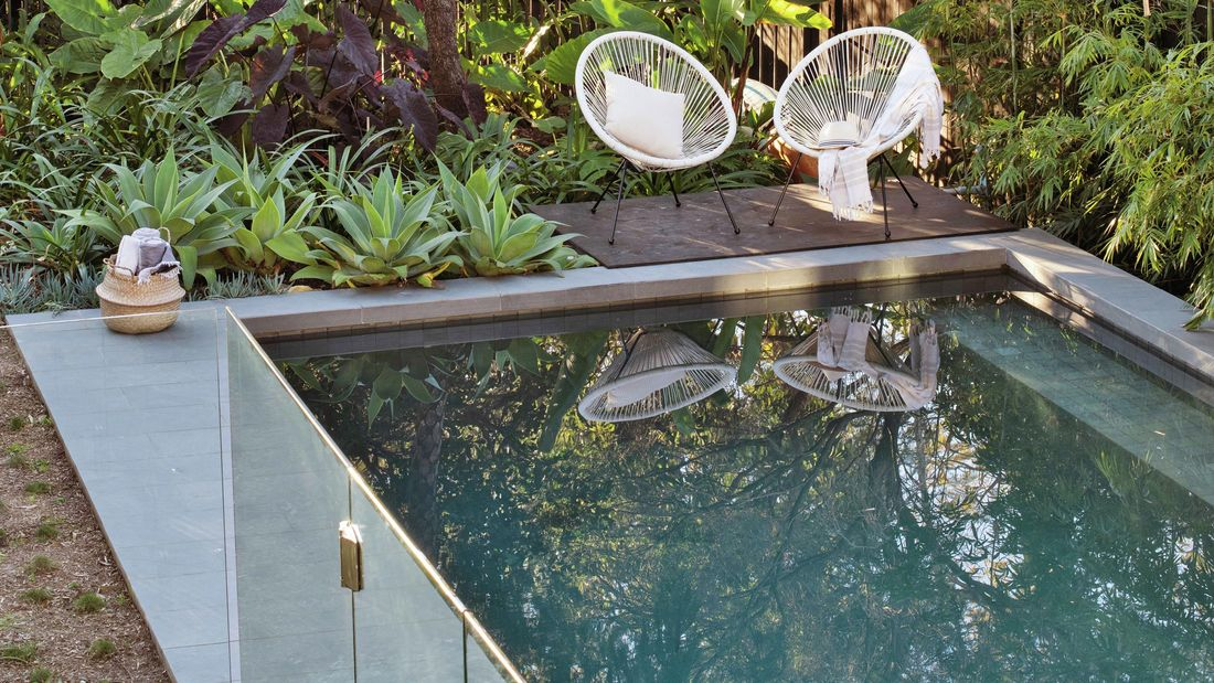 A pristine outdoor pool with deck chairs and lush green plants.