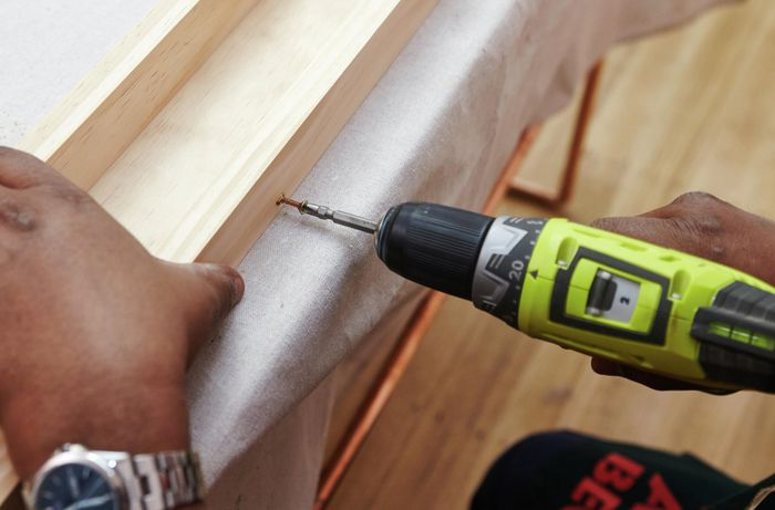 A person screwing into lengths of pine timber using a cordless drill