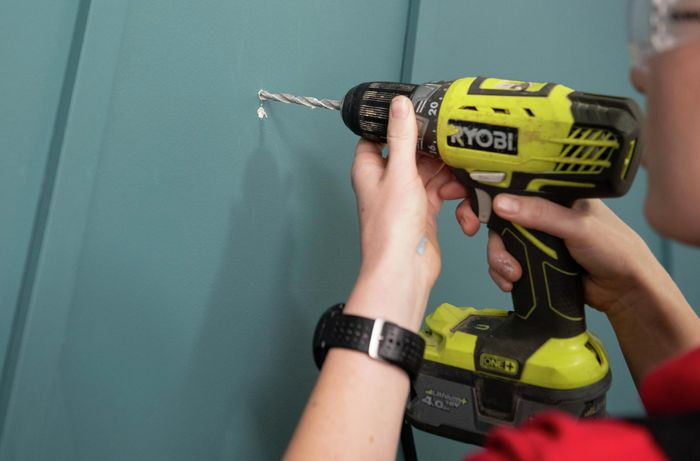 Person wearing safety glasses drilling into wall.