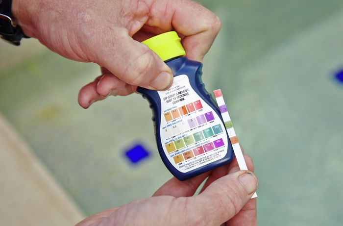 A pool test kit being used to measure the pH level, chlorine level, alkalinity and stabiliser