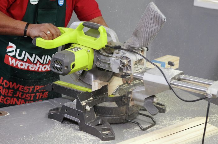 A person cutting pine timber with a drop saw