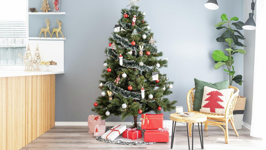 Traditional Christmas tree with handmade decorations set up in modern living room