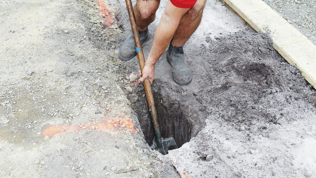 A posthole being dug out of the ground by a Bunnings team member with a shovel