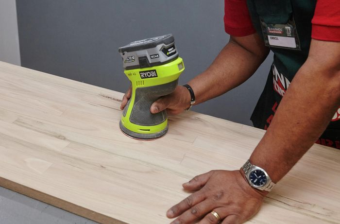 A person sanding a timber table top with orbital sander