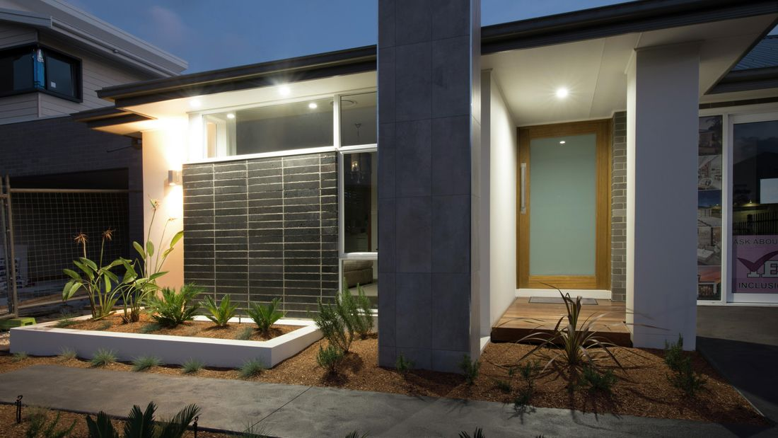 The exterior of a modern house with a frosted glass front door.