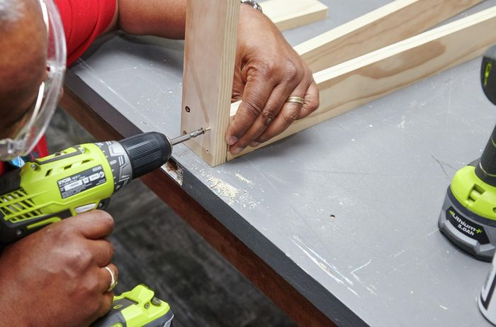 A person connecting two lengths of timber using a cordless driver