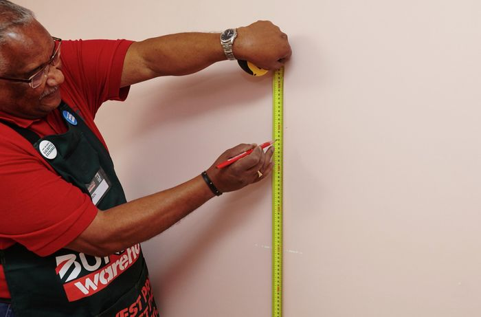 A person marking a measurement on a wall using a measuring tape