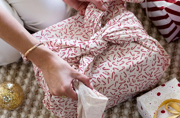 Tying red and white cloth together to cover a gift box.