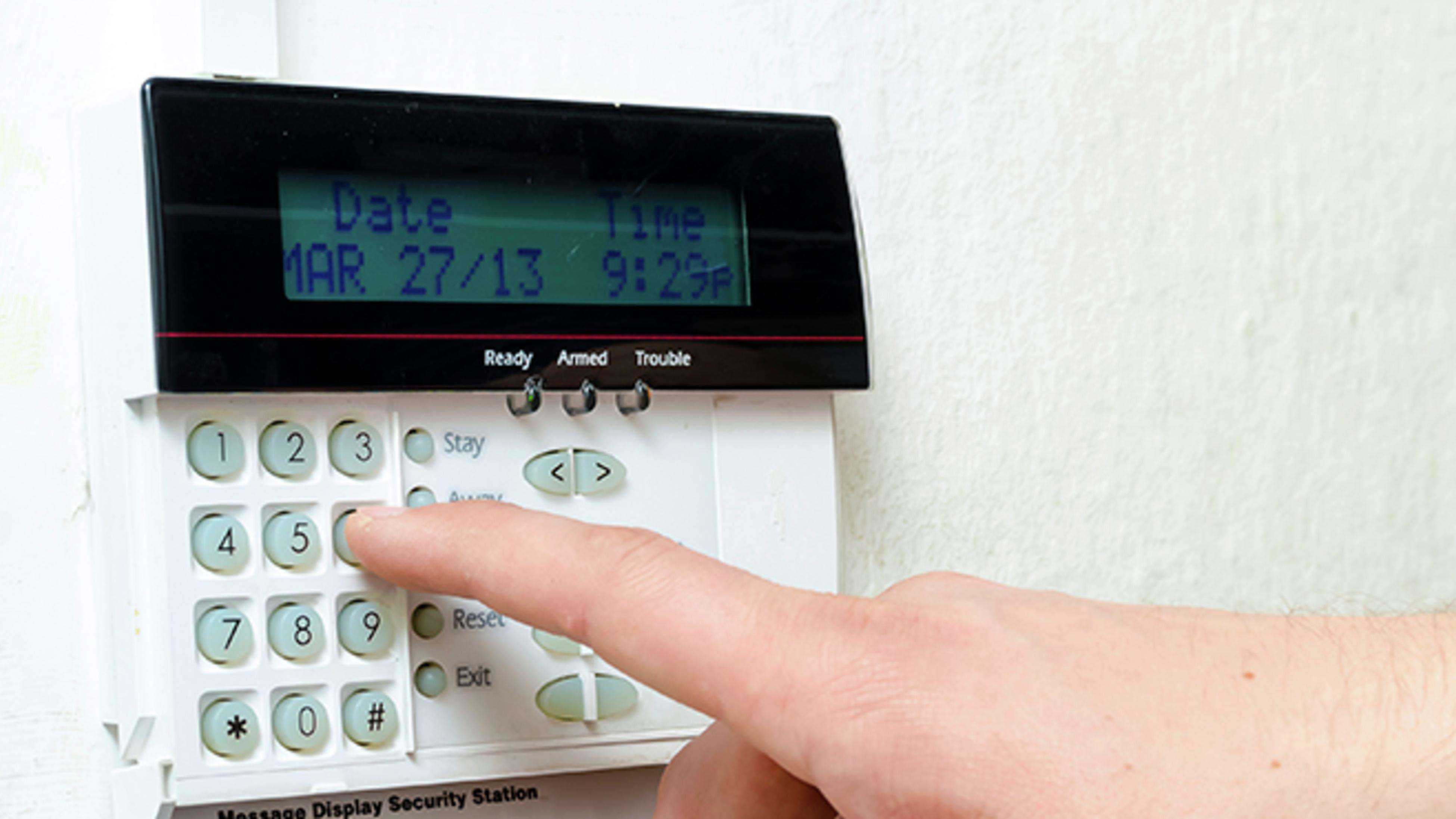 Alarm system with keypad and a person keying in a pin number.