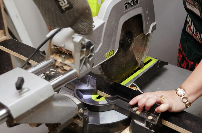 Person cutting form ply with circular saw.