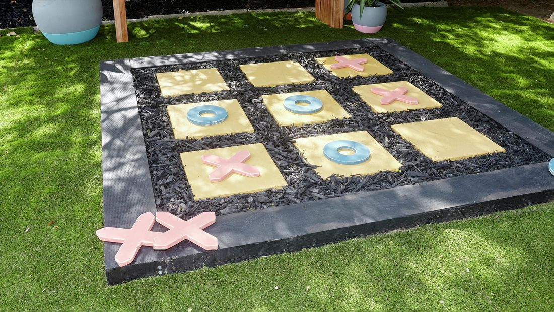 An outside noughts and crosses game made with pavers on a bed of sand with a border of sleepers