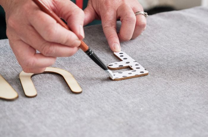 Person applying glue to wooden letter.