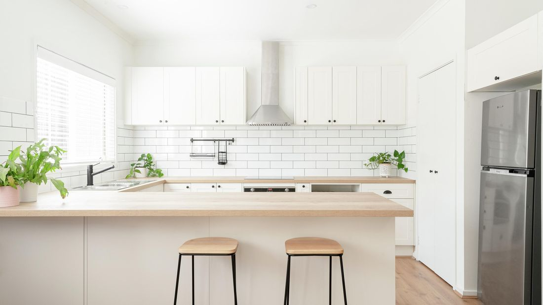 Kitchen with white cabinets, timber benchtop and white tile splashback.