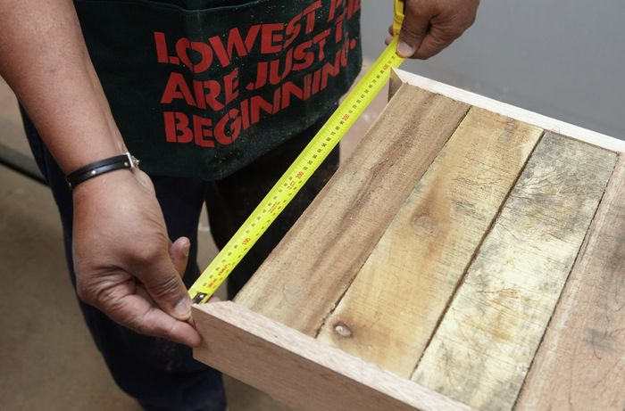 Person measuring width of tabletop