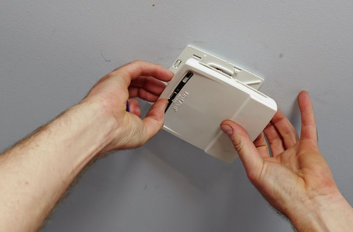 A smoke alarm being removed from its bracket in the ceiling