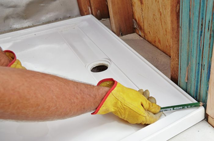 A pencil being used to mark cutting lines on a wall frame to make room for a shower base