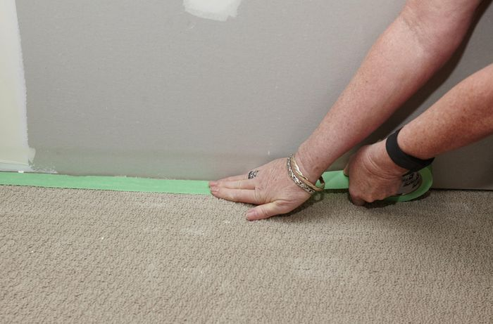 The edge of a floor being sealed ahead of an undercoat being applied to the wall above
