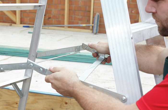 A person locking the horizontal arms on a ladder